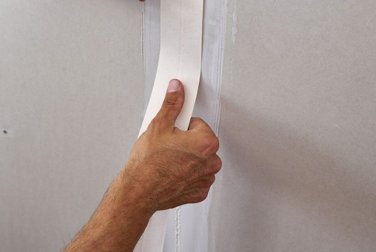 Applying tape on drywall seams.