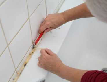 Removing silicone caulk from bathroom tiles with a razor.