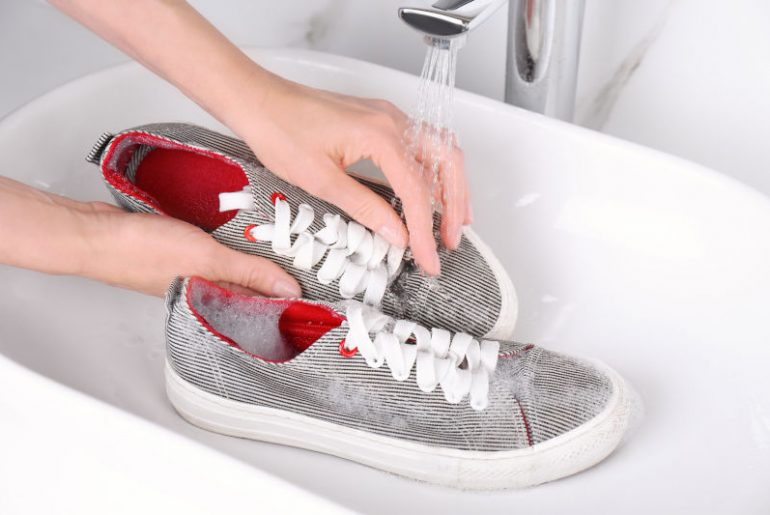 Washing sport shoes in a sink.